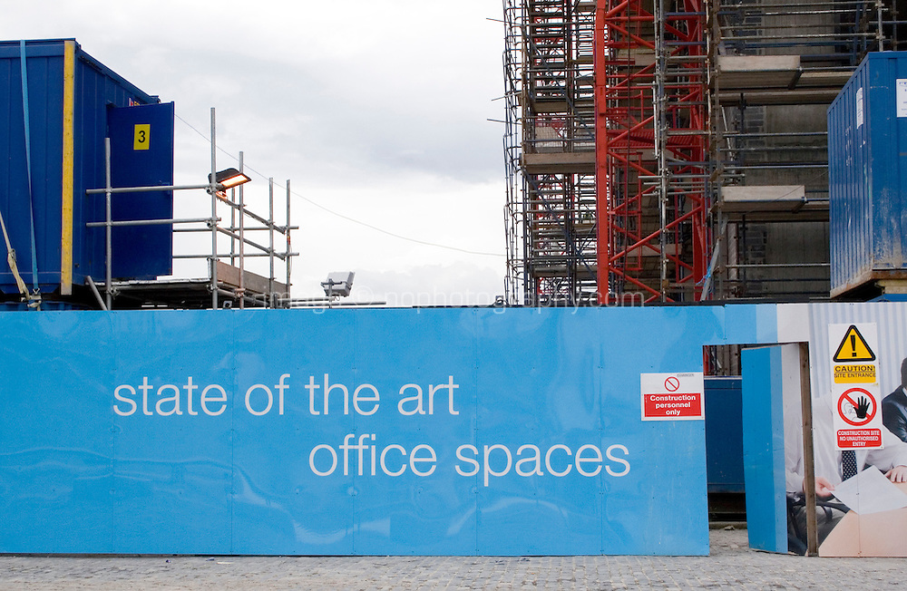 Hoarding around construction site for offices at the docklands in Dublin Ireland, sign reads state of the art office spaces