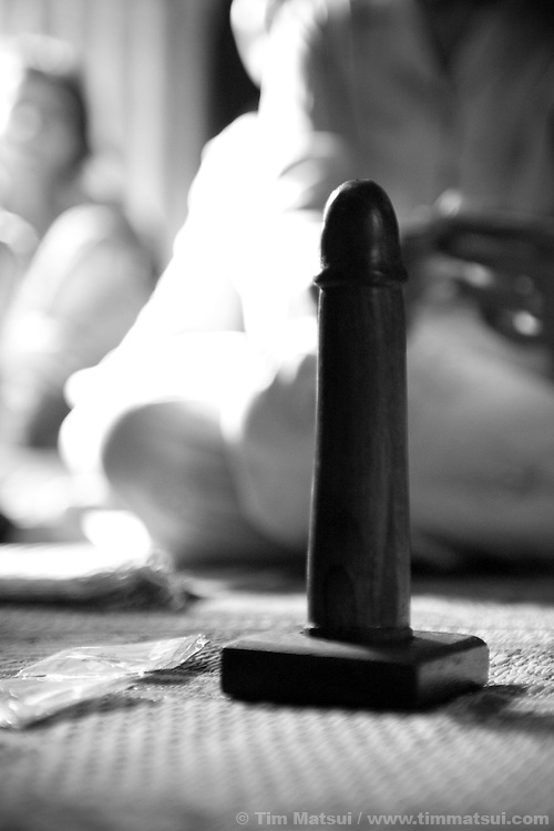 "A wooden penis to practice condom application rests on the floor of a prostitute's single-room home during a meeting with a social worker from the agency ""Acting for Women in Distressing Situations"" (AFESIP) which conducts outreach and provides services in Phnom Penh, Cambodia. The slum's permanent structure, a decaying four story building known simply as 'The Building', was built in the 1960's as transitional housing and now hosts a shantytown where many of the city's poor live, including many prostitutes, and is believed to have the highest rate of HIV infection in the city. AFESIP hands out free condoms, instructs prostitutes on HIV prevention, and conducts outreach in case the prostitutes need medical services, choose to leave their profession, or can report on cases of sex trafficking. AFESIP offers housing, education, training, and counseling for women who are victims of sex trafficking, worked as prostitutes, or are escaping domestic violence. Founded by Somaly Mam, who herself was once a prostitute and victim of trafficking and domestic abuse, AFESIP has three facilities in Cambodia and works with other NGO's to provide long term care for the women."