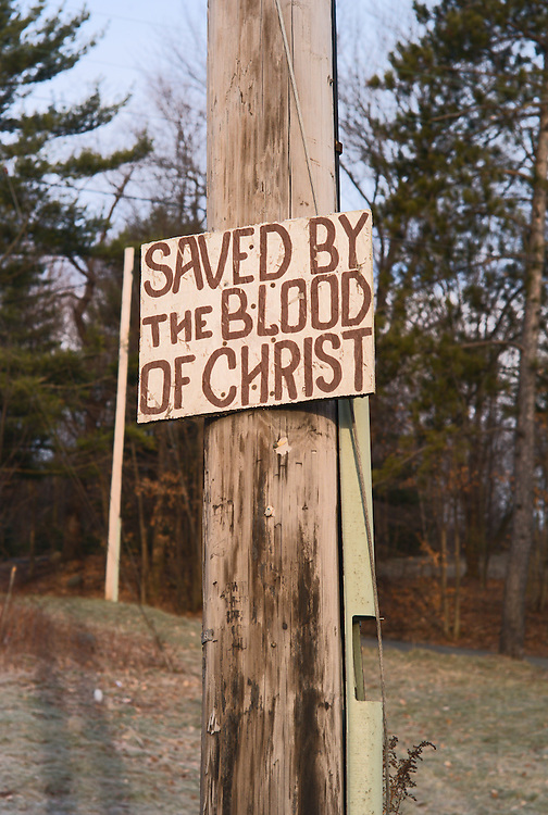 "Bible quotation on sign on telephone pole (""Saved by the blood of Christ"", Matthew 26:26-28; Romans 5:9)"