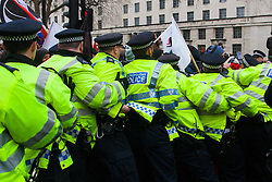 Whitehall, London, April 4th 2015. As PEGIDA UK holds a poorly attended rally on Whitehall, scores of police are called in to contain counter protesters from various London anti-fascist movements. PICTURED: Holding on to each other's belts, police form an blockade to prevent anti-fascists from attacking the small PEGIDA rally.