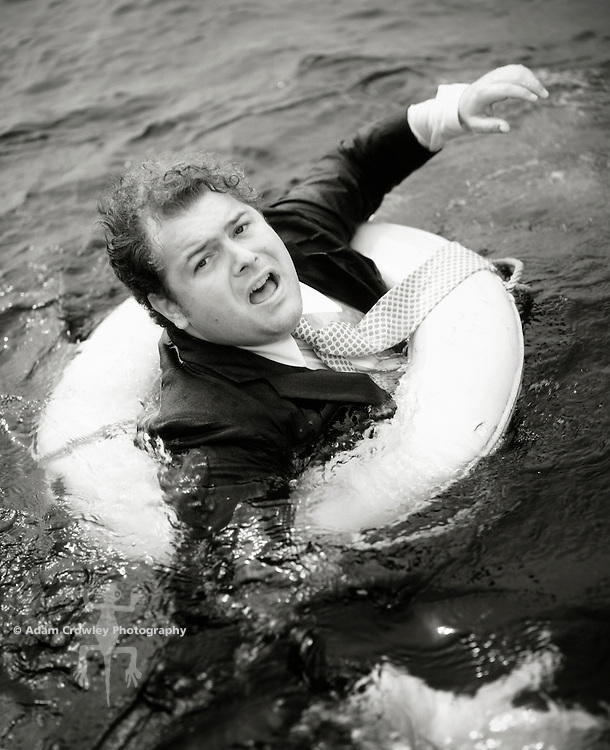 Businessman in water with life preserver