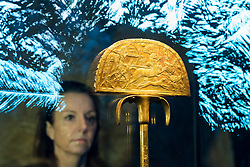 "© Licensed to London News Pictures. 01/11/2019. LONDON, UK. A woman views ""A Gilded Wooden Ostrich Hunt Fan"".  Preview of ""Tutankhamun, Treasures of the Golden Pharoah"" at the Saatchi Gallery in Chelsea.  The exhibition celebrates the 100th year anniversary of the opening of Tutankhamun's tomb and displays 150 works in the largest collection of Tutankhamun's treasures ever to leave Egypt.  The show runs 2 November to 3 May 2020.  Photo credit: Stephen Chung/LNP"