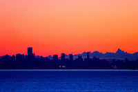 Vivid early dawn colours define Vancouver West End skyline, English Bay in foreground