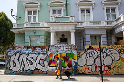 © Licensed to London News Pictures. 24/08/2019. London, UK. A woman walks past a business property boarded up ahead of the 2019 Notting Hill Carnival which takes place this weekend and on bank holiday Monday. Up to 1 million people are expected to attend the biggest street party in Europe. Photo credit: Dinendra Haria/LNP