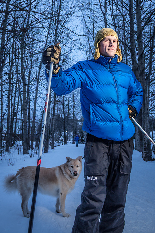 Small construction company owner, Cory Bernacchi with his dog, Teddy, on the Tony Knowles Coastal Trail near Westchester Lagoon, Anchorage