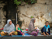 24 SEPTEMBER 2015 - BANGKOK, THAILAND:  Women and their children relax in front of Haroon Mosque before the celebration of Eid al-Adha at Haroon Mosque in Bangkok. Eid al-Adha is also called the Feast of Sacrifice, the Greater Eid or Baqar-Eid. It is the second of two religious holidays celebrated by Muslims worldwide each year. It honors the willingness of Abraham to sacrifice his son, as an act of submission to God's command. Goats, sheep and cows are sacrificed in a ritualistic manner after services in the mosque. The meat from the sacrificed animal is supposed to be divided into three parts. The family retains one third of the share; another third is given to relatives, friends and neighbors; and the remaining third is given to the poor and needy.    PHOTO BY JACK KURTZ
