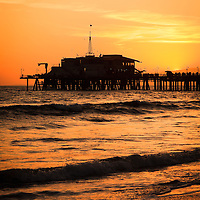 Photo of Santa Monica California Pier at sunset over the Pacific Ocean. The buildings at the end of Santa Monica Pier are the Mariasol restaurant and Harbor Office. Santa Monica Pier is a landmark located in Los Angeles County Southern California and has an amusement park with a ferris wheel, roller coaster, restaurants, and other attractions.