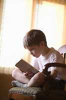 Boy sits cross-legged on chair reading book