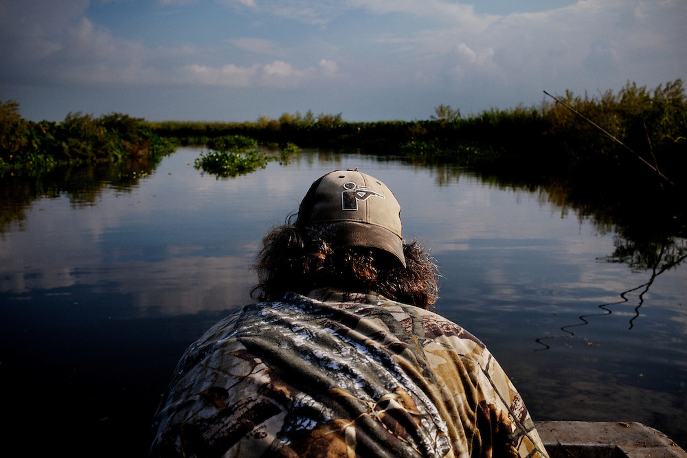 Rebel sits on the bow of the boat looking to see if a line is down, indicating that an alligator might be caught while gator hunting near Shell Island, Louisiana on Sunday, September 20, 2009.
