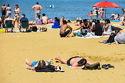 © Licensed to London News Pictures. 25/05/2020. LONDON, UK.  People take advantage of the easing of certain coronavirus pandemic lockdown restrictions to enjoy the sunshine and warm weather on Bank Holiday Monday at Ruislip Lido in north west London. The UK government continues to remind the public adhere to social distancing when outdoors and to wear a face covering where social distancing is not possible.  The forecast is for temperatures to rise to 25C, with similar conditions for the next few days.  Photo credit: Stephen Chung/LNP