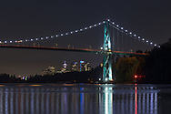 The Lions Gate Bridge and buildings in downtown Vancouver (Harbour Center, Shaw Tower, amoung others) after sunset. Photographed in the evening from Ambleside Park along the shoreline in West Vancouver, British Columbia, Canada.