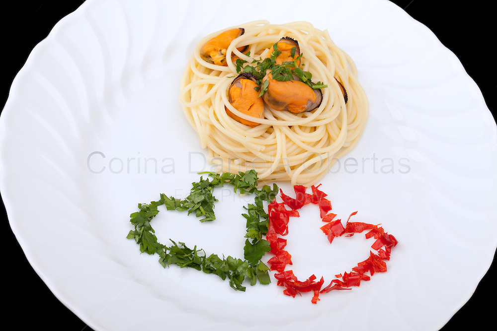 Italian Cuisine - First Courses - Pasta - Spaghetti with mussels decorated with hearts of parsley and chili pepper in order to have to colors of Italian flag.