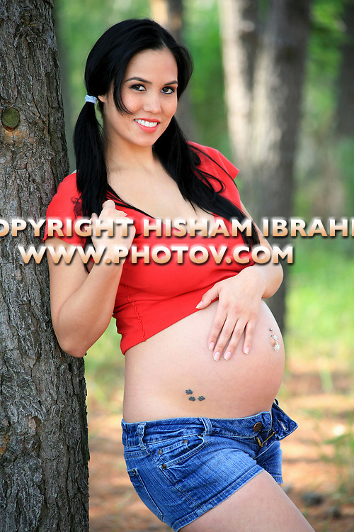 Young sexy pregnant woman standing in a park.