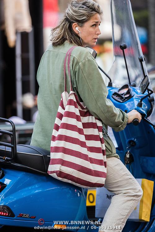NLD/Amsterdam/20160830 - zwangere zangeres Do op haar blauwe scooter in Amsterdam