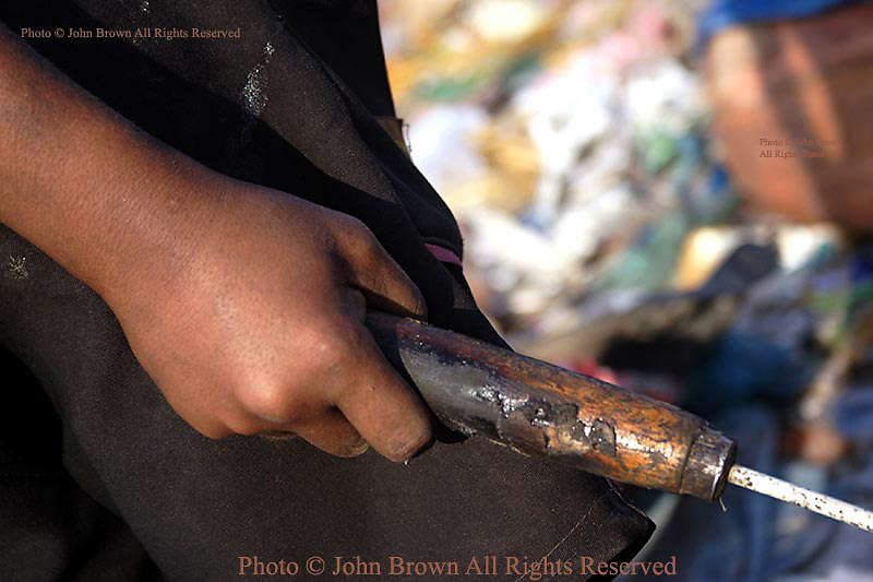 A young worker uses a large gaff, which he is using to collect soft clear plastic, at The Stung Meanchey Landfill in Phnom Penh, Cambodia. Over 700 tons of garbage is dumped there daily and roughly 600 children work at the dump on a daily basis. Most of the children are too poor to attend school.