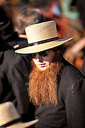 Amish man with a red beard bids on farm equipment during the Annual Mud Sale to support the Fire Department  in Gordonville, PA.