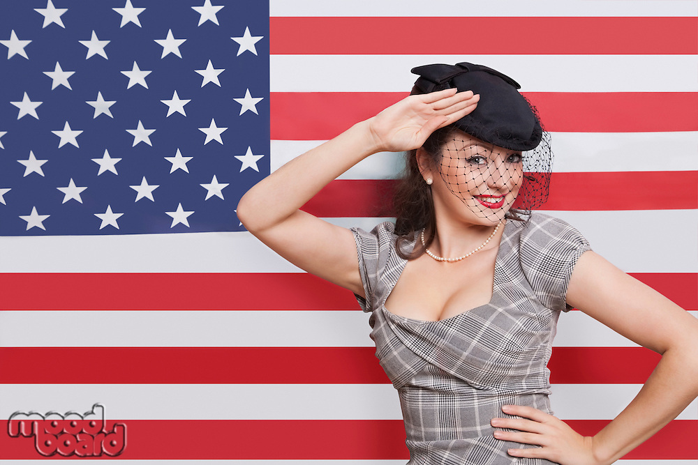 Portrait of young Caucasian woman with veiled hat saluting against American flag