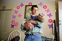 Oscar Ramirez Castaneda rocks his nine month old daughter Dulce Ramirez, in their home in Framingham, Massachusetts on May 13, 2012.  Oscar was adopted by Lieutenant  Oscar Ovidio Ramirez Ramos at the age of 3 after the Lieutenant and his fellow Kaibil troops led a massacre in young Oscar's village in Guatemala.  Matthew Healey for ProPublica