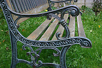 Wooden garden bench on grass in Irish garden<br />