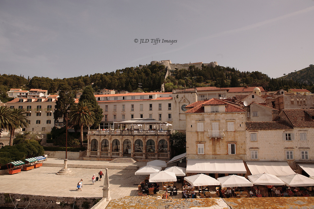 Hvar town square on the left, cafe umbrellas on right, mixed era government buildings. Above, the hill covered by the Spanjola Fortress overlooking the town.