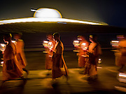 """22 FEBRUARY 2016 - KHLONG LUANG, PATHUM THANI, THAILAND: Buddhist monks participate in the candle light procession around the chedi during the Makha Bucha Day service at Wat Phra Dhammakaya.  Makha Bucha Day is a public holiday in Cambodia, Laos, Myanmar and Thailand. Many people go to the temple to perform merit-making activities on Makha Bucha Day, which marks four important events in Buddhism: 1,250 disciples came to see the Buddha without being summoned, all of them were Arhantas, Enlightened Ones, and all were ordained by the Buddha himself. The Buddha gave those Arhantas the principles of Buddhism, called """"The ovadhapatimokha"""". Those principles are:  1) To cease from all evil, 2) To do what is good, 3) To cleanse one's mind. The Buddha delivered an important sermon on that day which laid down the principles of the Buddhist teachings. In Thailand, this teaching has been dubbed the """"Heart of Buddhism."""" Wat Phra Dhammakaya is the center of the Dhammakaya Movement, a Buddhist sect founded in the 1970s and led by Phra Dhammachayo. The temple is famous for the design of its chedi, which some have likened to a flying saucer or UFO.                PHOTO BY JACK KURTZ"""