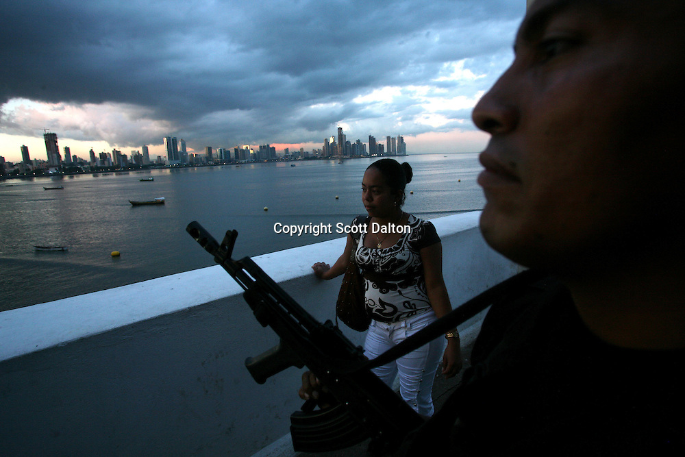 A woman looks out on the ocean as a presidential guard keeps watch in Panama City, Panama on Thursday, September 6, 2007. (Photo/Scott Dalton).