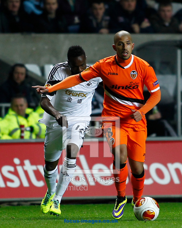 Picture by Mike  Griffiths/Focus Images Ltd +44 7766 223933<br /> 28/11/2013<br /> Roland Lamah of Swansea City and Sofiane Feghouli of Valencia Club de F&uacute;tbol during the UEFA Europa League match at the Liberty Stadium, Swansea.