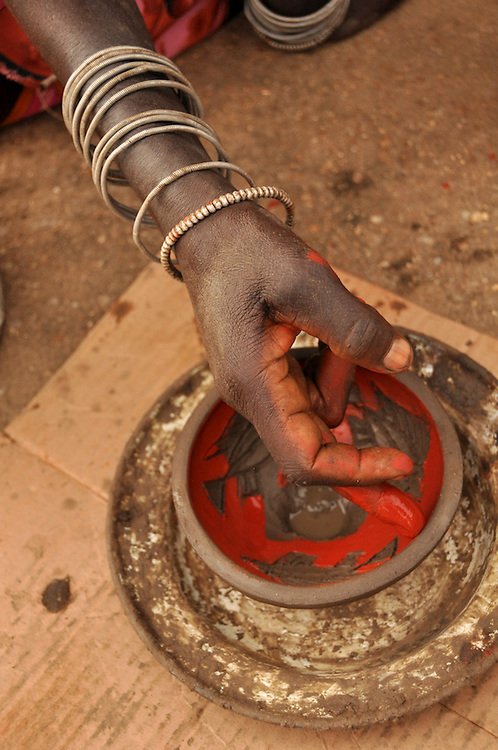 A woman from Mashamba Village Pottery carefully paints the wet clay with red ochre to add a design around the fish inside. She is wearing traditional Venda bracelets. Limpopo, South Africa