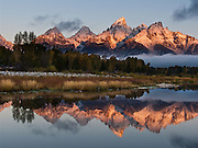 Mountain peaks reflect in the Snake River at Schwabacher Landing at sunrise, Grand Teton National Park, Wyoming, USA