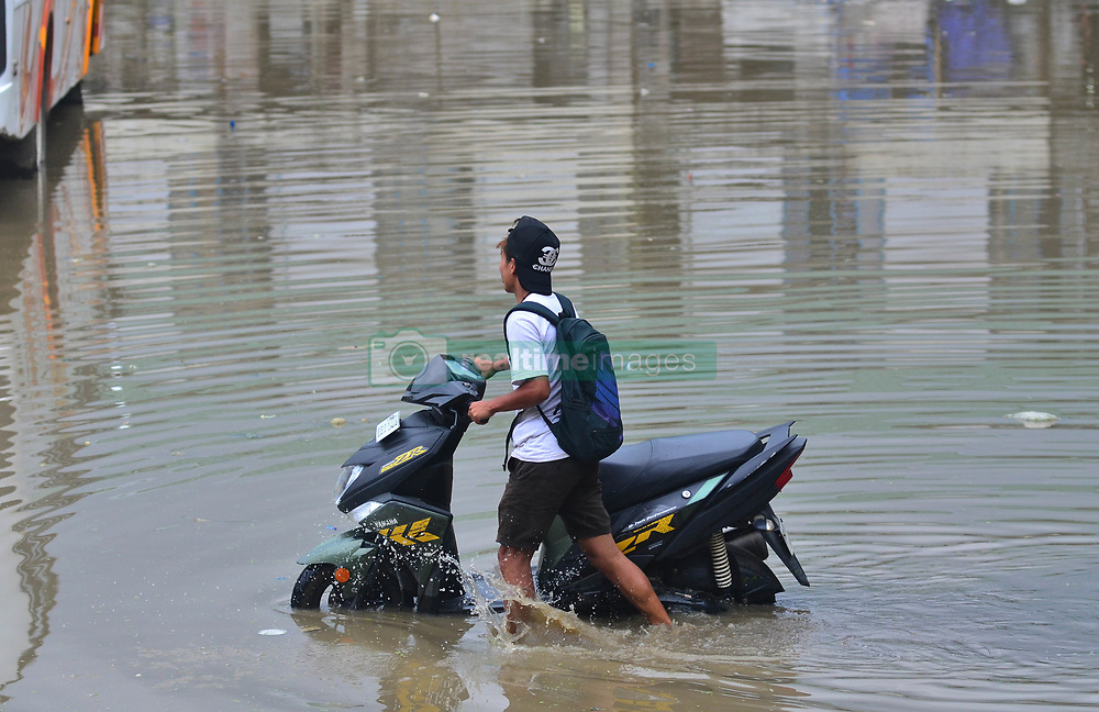 May 25, 2019 - Dimapur, Nagaland, India - A motorist pushes his cycle in a flooded compound after a heavy shower in Dimapur, Nagaland on Saturday, 25 May 2019. Photo by Caisii Mao  (Credit Image: © Caisii Mao/NurPhoto via ZUMA Press)