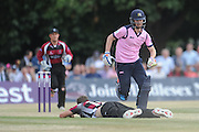 Andy Balbirnie runs past Jamie Overton who lays flat on the ground during the NatWest T20 Blast South Group match between Middlesex County Cricket Club and Somerset County Cricket Club at Uxbridge Cricket Ground, Uxbridge, United Kingdom on 26 June 2015. Photo by David Vokes.