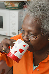 Elderly lady drinking tea.