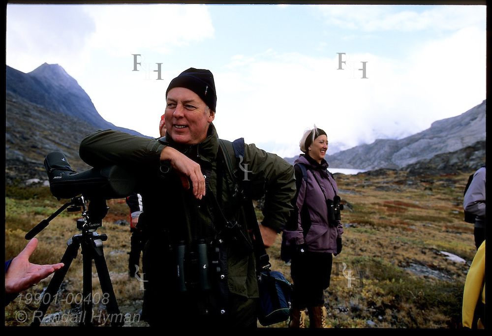 Ornithologist Chris Harbard rests on spotting scope while guiding cruise line passengers on hike at Tasiusaq Bay, western Greenland