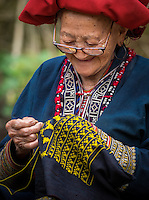 SAPA, VIETNAM - CIRCA SEPTEMBER 2014:  Old woman from the Red Dao minority knitting in Ta Phin Village near Sapa, north Vietnam.