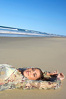 Young woman lying on beach head and shoulders