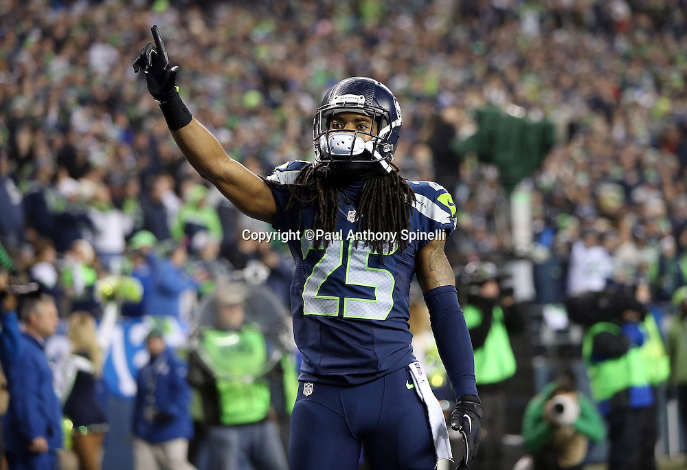 Seattle Seahawks cornerback Richard Sherman (25) points number one with his index finger as he celebrates after Seattle Seahawks free safety Earl Thomas (29) intercepts a late second quarter pass during the NFL week 19 NFC Divisional Playoff football game against the Carolina Panthers on Saturday, Jan. 10, 2015 in Seattle. The Seahawks won the game 31-17. ©Paul Anthony Spinelli