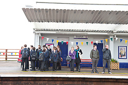 © Licensed to London News Pictures. 04/04/2014. Dawlish, Devon, UK. Peopl wait for a train. The Riviera Line railway linking Exeter, Plymouth and Penzance reopens two weeks ahead of schedule and two months after a sea wall was breached and a stretch of the line was badly damaged at Dawlish on February 4th 2014  by large waves and storms  which hit much of the British coastline on 4th February 2014. Photo credit : Graham M. Lawrence/LNP