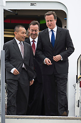 © London News Pictures. 09/07/2012. Farnborough, UK. British Prime Minister David Cameron (right) leaving a Malaysian Airlines A380 Airbus with Ahmad Jauhari Yahya CEO of Malaysia Airlines (left) and Fabrice Bregier CEO of Airbus (centre) during a walk round of aircraft on day one of the Farnborough International Airshow, in Farnborough, Hampshire, UK on July 9, 2012. FIA is a seven-day international trade fair for the aerospace industry which is held every two years at Farnborough Airport . Photo credit: Ben Cawthra/LNP.
