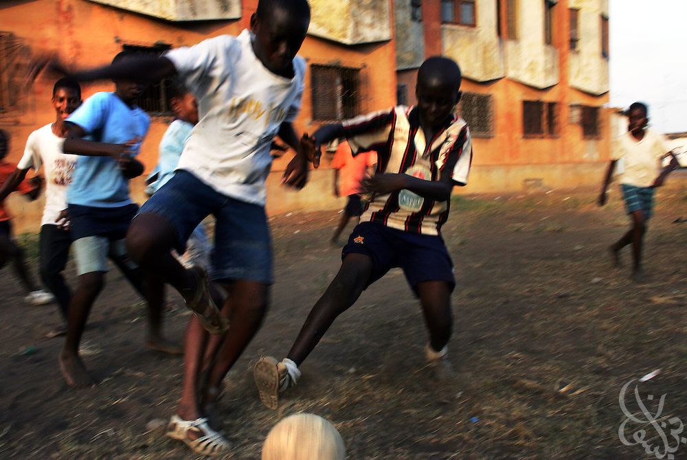 "Ivorian boys wearing plastic shoes called ""korodjo"" play a game of street football in a poor district of the Port Bouet neighborhood of Abidjan, Côte d'Ivoire February 17,2006. Football is an integral part of the social fabric that makes up Ivorian society."