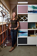 Mara Lavitt /For Hearst Connecticut<br /> February 23, 2016<br /> Marci Klein of Fairfield, the owner, designer and maker at her business Modify Furniture, Bridgeport with one of her Polychrome case units.