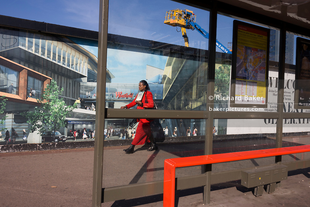 Local lady passes a hoarding showing aspiration and consumerism of nearby Westfield City shopping complex, Stratford