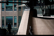 Smokers in a quiet corner of the Broadgate corporate offices development in the City of London. As the man exhales, blowing a plume of blue smoke up into the air above his head, he talks to a woman associate, both in a corner, under the tall steel architecture with the backdrop of the Broadgate development within the ancient boundary of the capital's Square Mile, it's financial district founded by the Romans in AD43.