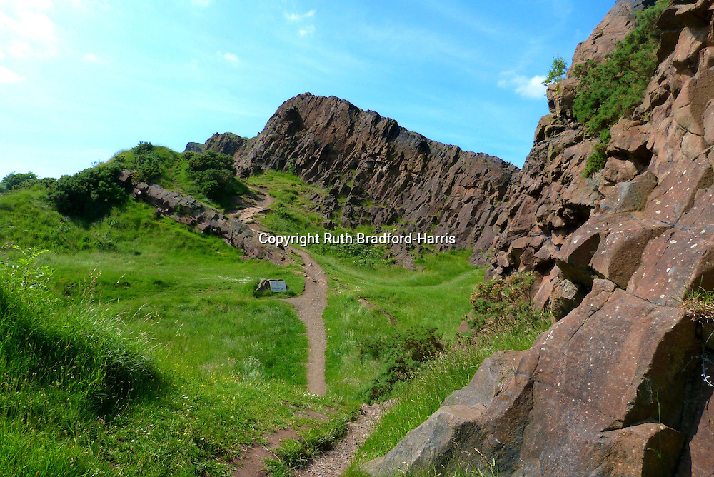 This view along the spectacular Salisbury Crags in Edinburgh shows successive folds of inclined cliffs opening up one after another into the distance. The Salisbury Crags are a sill of teschenite rock intruded in molten form into existing sandstone strata during ancient volcanic activity, tilted at an angle of 25 degrees by subsequent earth movements. Hutton's Section, an outcrop used by James Hutton to prove his ground-breaking 'Theory of the Earth' in 1788, is at centre left. The winding footpath which follows the gloriously undulating landscape around the base of the cliffs, is known as Radical Road.<br />