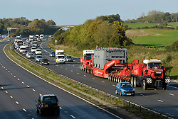 © Licensed to London News Pictures.  27/10/2013.  M4 motorway, South Gloucestershire.  An electricity transformer, one of the biggest abnormal loads ever transported on the roads is driven down the M4 on Sunday morning, causing traffic tailbacks behind. The giant transformer was taken from Avonmouth Docks to a substation in Melksham to the Westlands Lane electricity plant.  The huge transporter, described by police in Wiltshire as 'one of the largest loads to ever be moved' measured 5.1 metres wide, almost 17ft, was about 65 metres, or 213ft long, and weighed 254 tonnes.  27 October 2013.<br /> Photo credit : Simon Chapman/LNP
