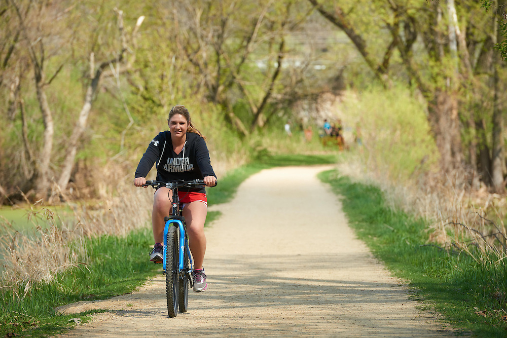Activity; Biking; Buildings; Bluffs; Marsh; Location; Outside; Objects; Bike; People; Student Students; Woman Women; Spring; April; Time/Weather; day; Type of Photography; Candid; UWL UW-L UW-La Crosse University of Wisconsin-La Crosse