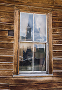"An old window reflects the Methodist Church steeple at Bodie, California's official state gold rush ghost town. Bodie State Historic Park lies in the Bodie Hills east of the Sierra Nevada mountain range in Mono County, near Bridgeport, California, USA. After W. S. Bodey's original gold discovery in 1859, profitable gold ore discoveries in 1876 and 1878 transformed ""Bodie"" from an isolated mining camp to a Wild West boomtown. By 1879, Bodie had a population of 5000-7000 people with 2000 buildings. At its peak, 65 saloons lined Main Street, which was a mile long. Bodie declined rapidly 1912-1917 and the last mine closed in 1942. Bodie became a National Historic Landmark in 1961 and Bodie State Historic Park in 1962."