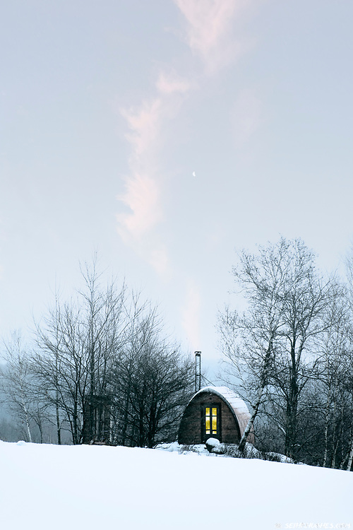 A warm glowing light inside a small cabin retreat with chimney smoke on a snow covered hillside.