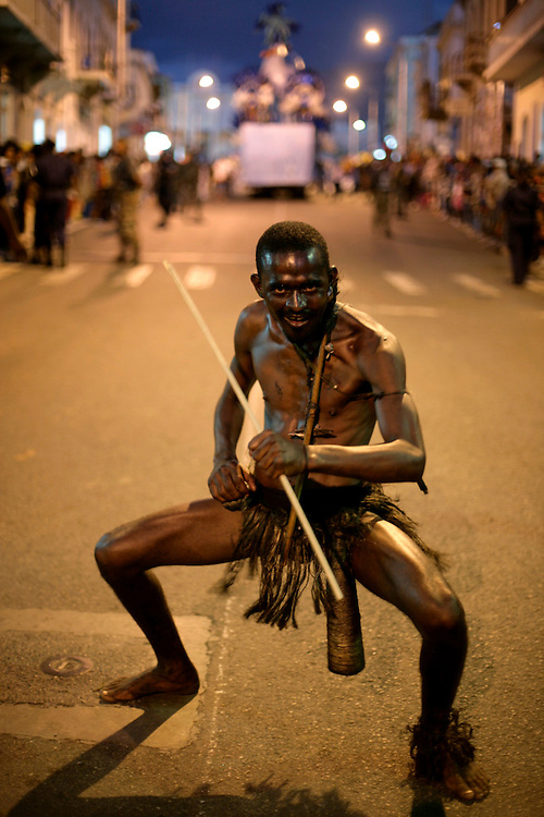 "In Carnival parades in Mindelo, attempts to recover the tradition of ""mandigas"" groups are made. These were members of African groups also used as slaves in Cape Verde. They rumble the streets chaotically playing with the audience. They are generally from the poorer strata of population."