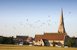 © Licensed to London News Pictures. 07/06/2015. London, UK. Hot air balloons rise over a church in Blackheath south east London on a summer morning. 50 Balloons took to the skies as part of the Lord Mayor's Regatta to raise money for charity. the last mass ascent balloon flight over London was over 20 years ago. Photo credit : Stu Mayhew/LNP