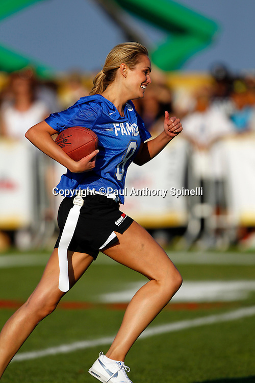 Actress Ashlan Gorse (8) of the Famers team runs the ball as she plays flag football in the EA Sports Madden NFL 11 Launch celebrity and NFL player flag football game held at Malibu Bluffs State Park on July 22, 2010 in Malibu, California. (©Paul Anthony Spinelli)